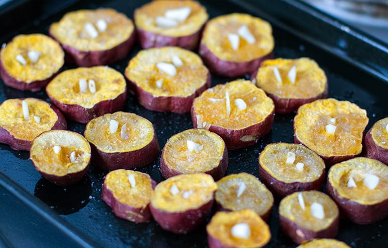 Garlic sweet potatoes - inserting garlic into almost cooked potatoes when roasting