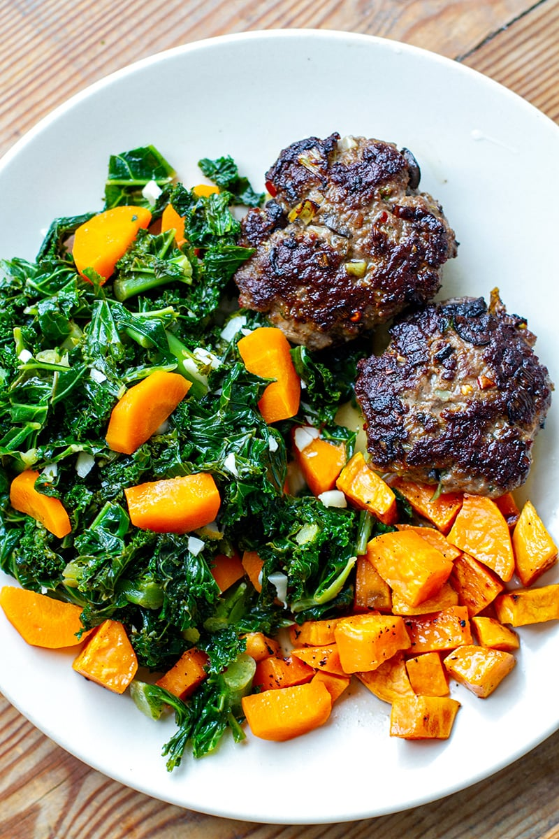 Whole30 dinner of beef burgers with garlic kale and sweet potatoes