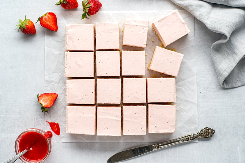 Sliced cheesecake bars with fresh strawberries