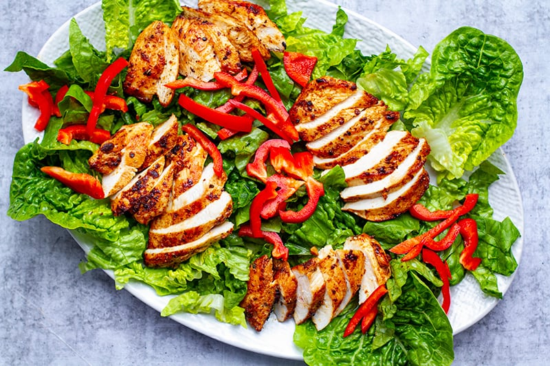 Arranging a Cobb salad on a plate with lettuce, chicken and peppers
